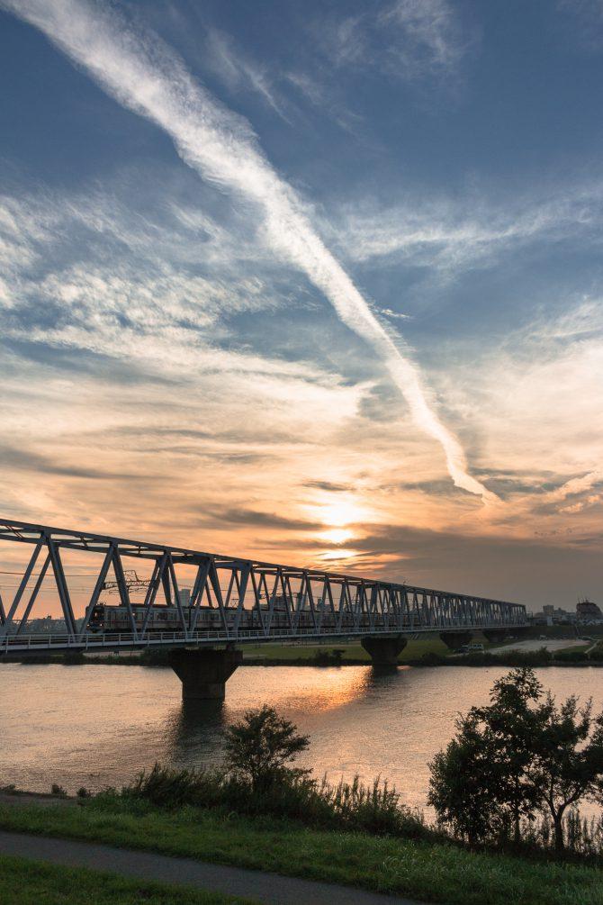 にじむ飛行機雲と京成線