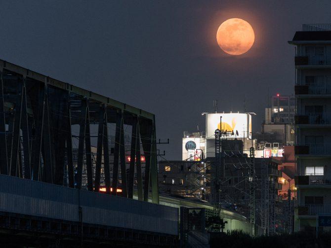 のぼりたての満月と総武線の橋
